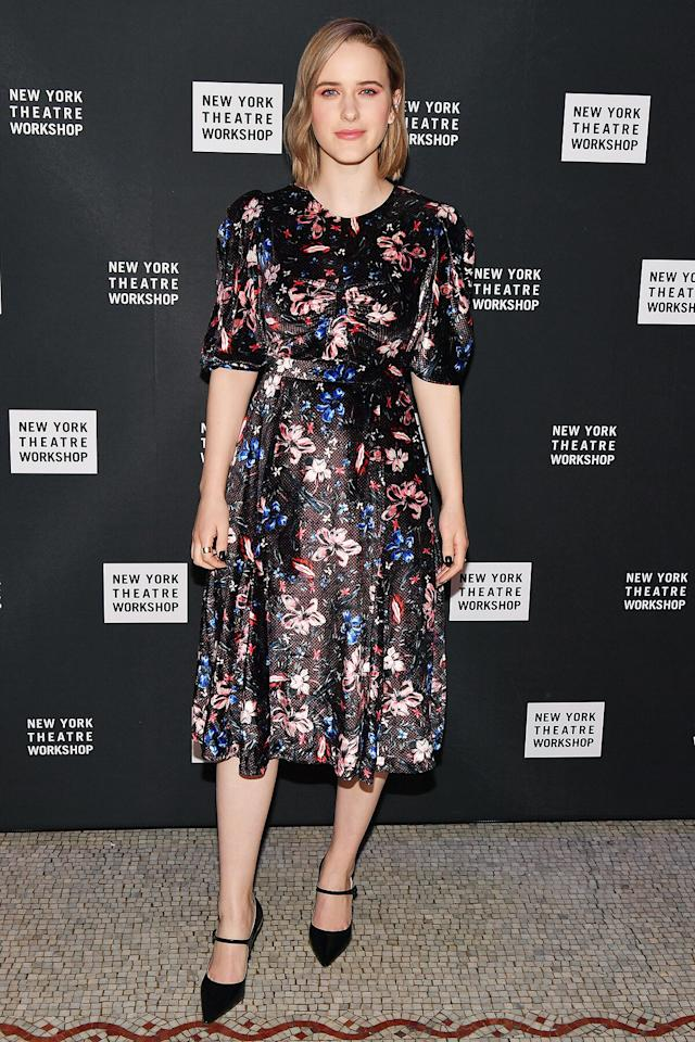 wears a black floral midi dress and black Mary Jane pumps at the New York Theater Workshop Gala in N.Y.C.