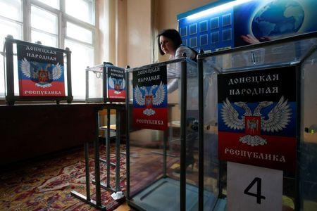 A member of a local electoral commission takes part in the preparations for the upcoming election, with stickers displaying symbols of the self-proclaimed Donetsk People's Republic seen on ballot boxes, at a polling station in Donetsk, eastern Ukraine, October 31, 2014.  REUTERS/Maxim Zmeyev
