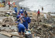 Workers remove debris washed ashore in Manila after Typhoon Yutu made landfall further to the north