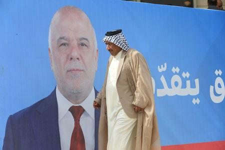 A man walks past a campaign poster of Iraqi Prime Minister Haidar al Abadi ahead of the parliamentary election in Najaf Iraq