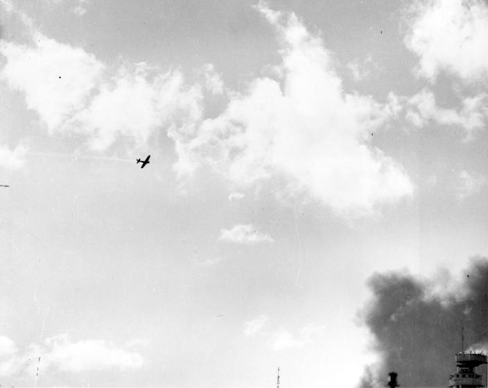 <p>A Japanese Type 00 (Zero) carrier fighter trails smoke after it was hit by anti-aircraft fire during the attack on Pearl Harbor on Dec. 7, 1941. (U.S. Navy/National Archives/Handout via Reuters) </p>