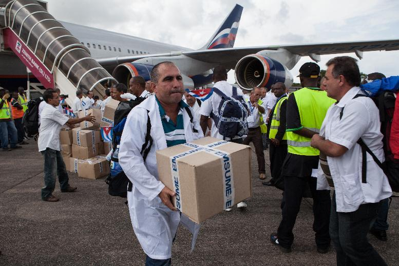 The first members of a team of 165 Cuban doctors and health workers unload boxes of medicine and medical material from a plane upon their arrival at Freetown's airport to help the fight against Ebola in Sierra Leone, on October 2, 2014 (AFP Photo/Florian Plaucheur)
