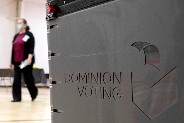 A worker passes a Dominion Voting ballot scanner while setting up a polling location at an elementary school in Gwinnett County, Georgia (AP)