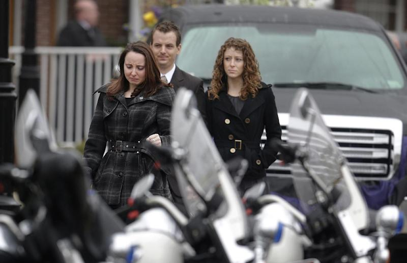 Mourners walk past police motorcycles as they depart St. Patrick's Church in Stoneham, Mass., following a funeral Mass for Massachusetts Institute of Technology police officer Sean Collier, Tuesday, April 23, 2013. Collier was fatally shot on the MIT campus Thursday, April 18, 2013. Authorities allege that the Boston Marathon bombing suspects were responsible. A truck that belonged to Collier sits behind. (AP Photo/Steven Senne)