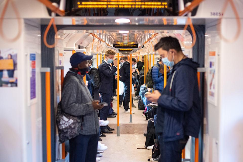 Commuters on board a London Overground train after Prime Minister Boris Johnson announced a range of new restrictions to combat the rise in coronavirus cases in England (PA)