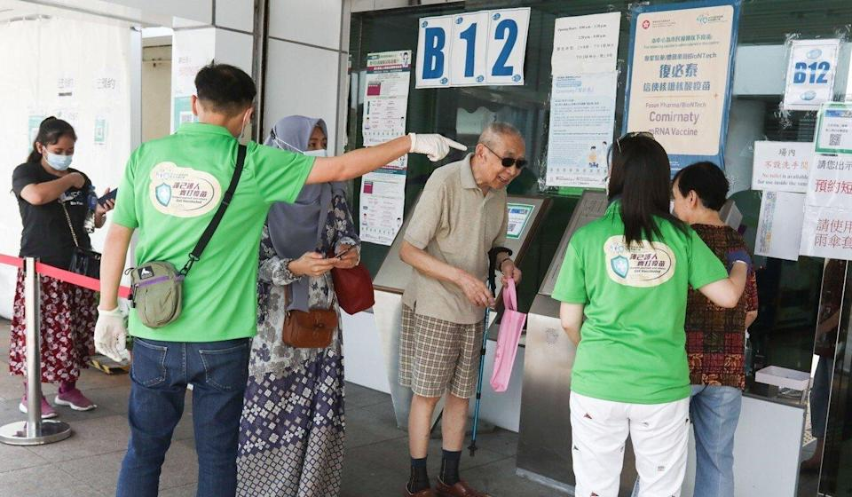 Residents are helped outside the BioNTech vaccination at the Lai Chi Kok Sports Centre. Photo: Jonathan Wong