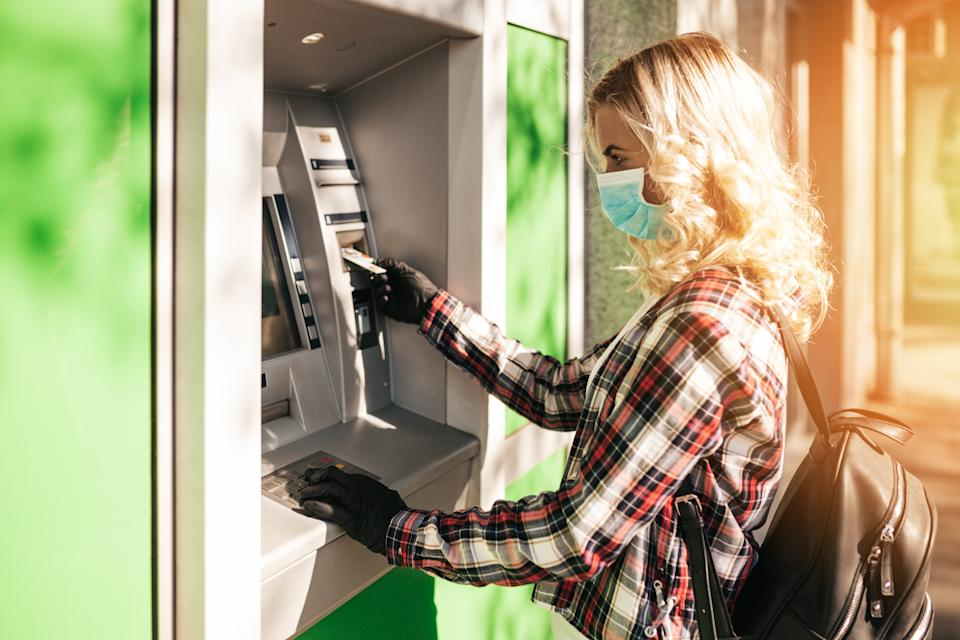 Young blonde woman with protective mask and gloves standing on city street and using ATM machine to withdraw cash. Corona or Covid-19 virus pandemic concept.