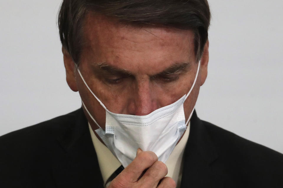 Brazil's President Jair Bolsonaro adjusts his mask during a ceremony about the extension of emergency aid to help the poor population affected by the COVID-19 pandemic, at the Planalto Presidential Palace, in Brasilia, Brazil, Tuesday, Sept. 1, 2020. (AP Photo/Eraldo Peres)