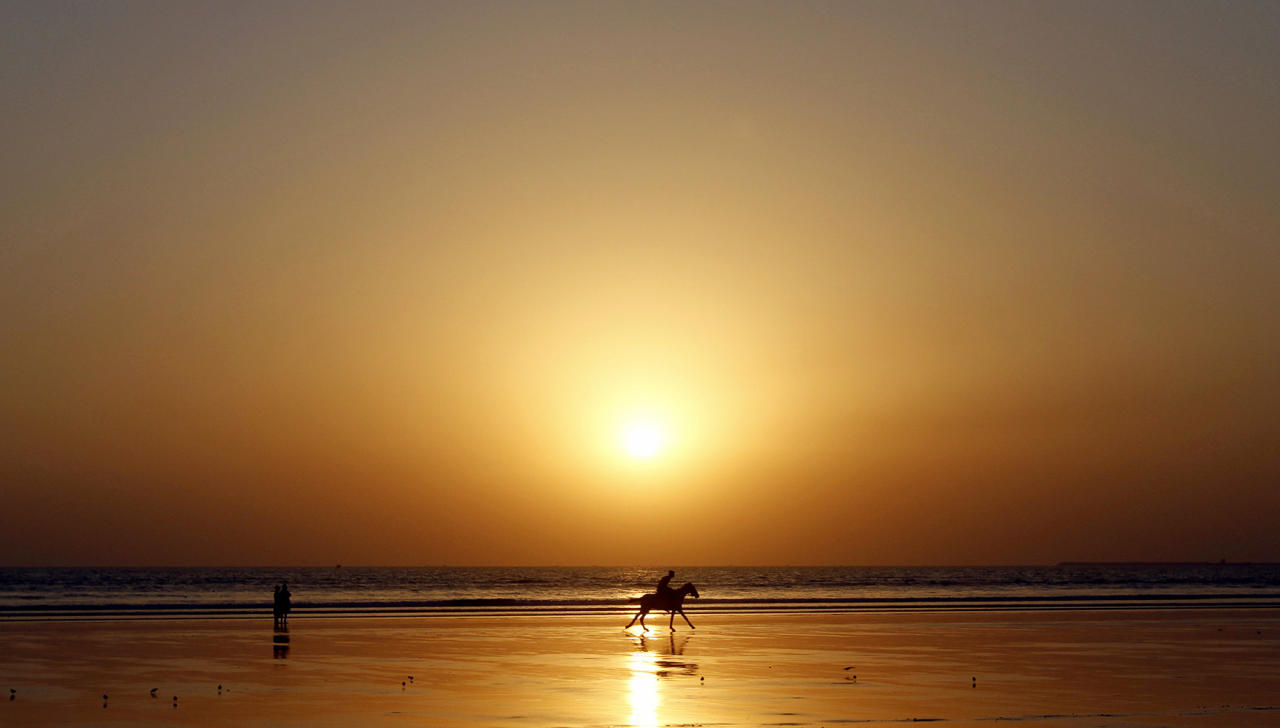 <p>A Pakistani man rides a horse along the beach of Karachi, Pakistan as the sun sets, Jan. 2, 2013. (AP Photo/Shakil Adil) </p>