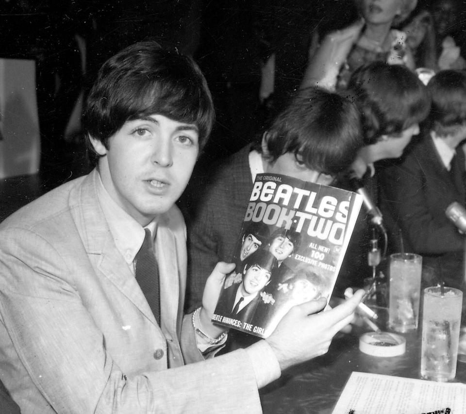 <p>Paul McCartney autographs a Beatles book backstage at their Hollywood Bowl concert on August 23rd, 1964.</p>