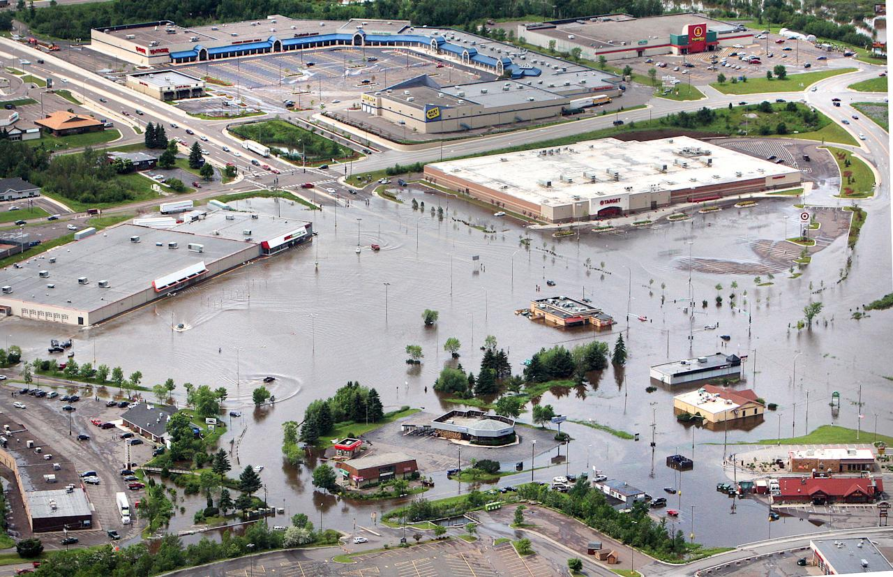 In this aerial photo, floodwaters surround the Burning Tree Plaza shopping area in Duluth, Minn., Wednesday afternoon, June 20, 2012. Residents evacuated their homes and animals escaped from pens at a zoo as floods fed by a steady torrential downpour struck northeastern Minnesota, inundating the city of Duluth, officials said Wednesday. (AP Photo/The Duluth News-Tribune, Bob King)