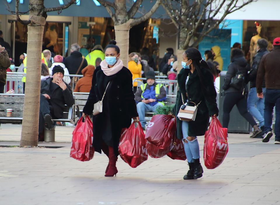 Women wearing face masks carry several shopping bags while walking on the street. On the first weekend of new coronavirus restrictions, the City of Coventry is in the Tier 3 - 'very high risk' with no pubs or restaurants are allowed to trade, except for takeaways, but all shops are open and shoppers out in force. (Photo by Keith Mayhew / SOPA Images/Sipa USA)