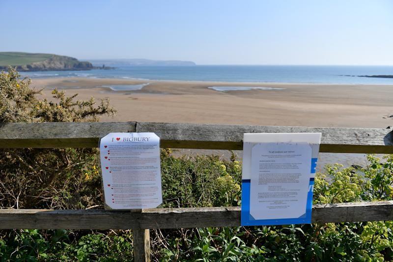 BIGBURY-ON-SEA, ENGLAND - APRIL 10: Signs are displayed informing visitors of Covid-19 measures above a deserted Bigbury Beach on April 10, 2020 in Bigbury-On-Sea, England. Public Easter events have been cancelled across the country, with the government urging the public to respect lockdown measures by celebrating the holiday in their homes. Over 1.5 million people across the world have been infected with the COVID-19 coronavirus, with over 7,000 fatalities recorded in the United Kingdom. (Photo by Dan Mullan/Getty Images)