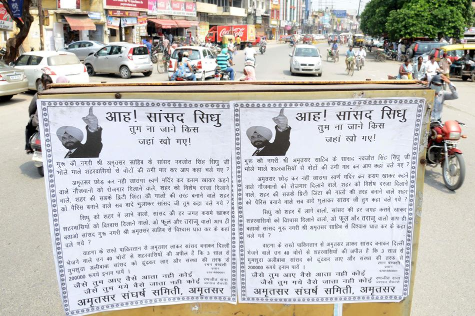 Indian commuters pass posters of former Indian cricketer and  Member of Parliament Navjot Singh Sidhu, the posters written in Hindi with Sidhu's pictures pointing to how Sidhu has allegedly cheated his voters, on a road in Amritsar, Punjab, on August 26, 2013. Sidhu is a Member of Parliament from Amritsar. AFP PHOTO/ NARINDER NANU