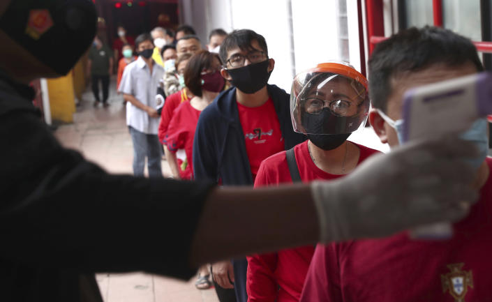 A security guard checks the temperature of worshippers at the entrance of a temple amid concerns of coronavirus outbreak during the Lunar New Year of the Ox celebrations in the China Town area of Jakarta, Indonesia, Friday, Feb. 12, 2021. (AP Photo/Tatan Syuflana)