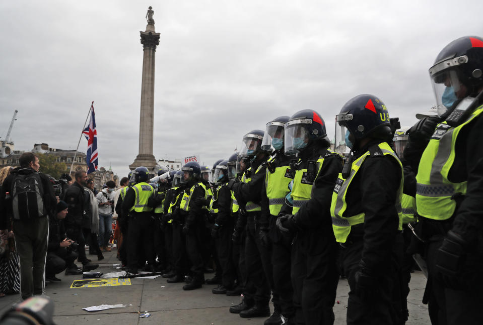 Riot police faces protesters who took part in a 'We Do Not Consent' rally at Trafalgar Square, organised by Stop New Normal, to protest against coronavirus restrictions, in London, Saturday, Sept. 26, 2020. (AP Photo/Frank Augstein)