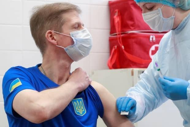 Oleksandr Petriv, a member of the Ukrainian Olympic shooting team that will compete in the Tokyo 2020 Olympics, waits before receiving a dose of Chinese-developed CoronaVac vaccine.