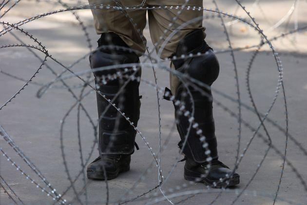 An Indian police officer stands behind the concertina wire during restrictions on Eid-al-Adha after the scrapping of the special constitutional status for Kashmir by the Indian government, in Srinagar, August 12, 2019.