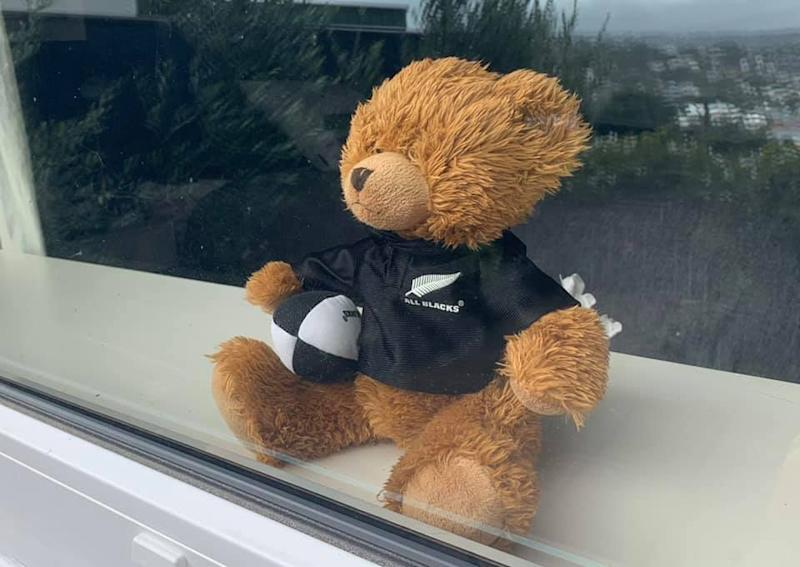 A stuffed bear wearing an All Blacks rugby jersey sits on a window sill.