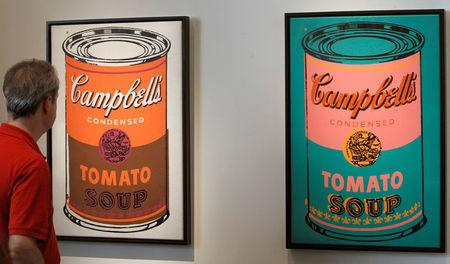 FILE PHOTO: A man looks at two paintings 'Coloured Campbell's soup can' by late U.S. artist Andy Warhol the Art Unlimited of the Art Basel art fair in Basel