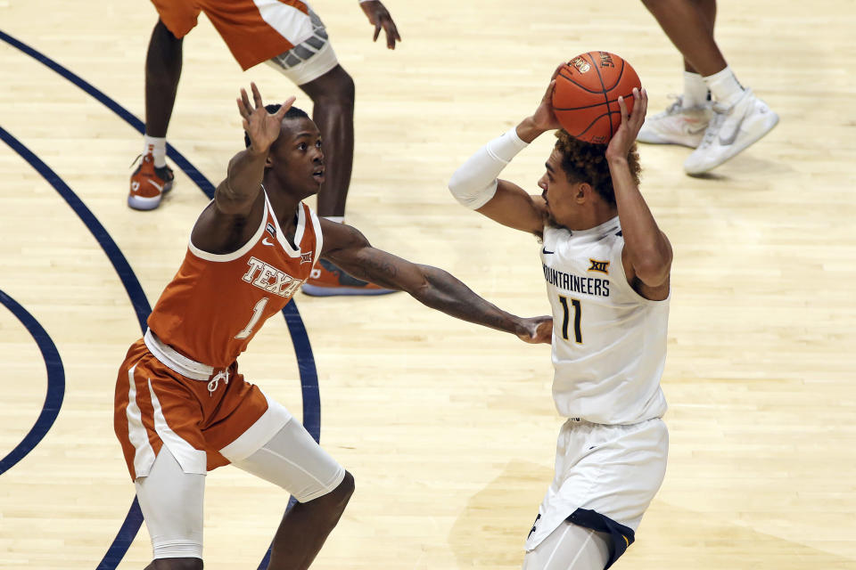 West Virginia forward Emmitt Matthews Jr. (11) passes while defended by Texas guard Andrew Jones (1) during the half of an NCAA college basketball game Saturday, Jan. 9, 2021, in Morgantown, W.Va. (AP Photo/Kathleen Batten)