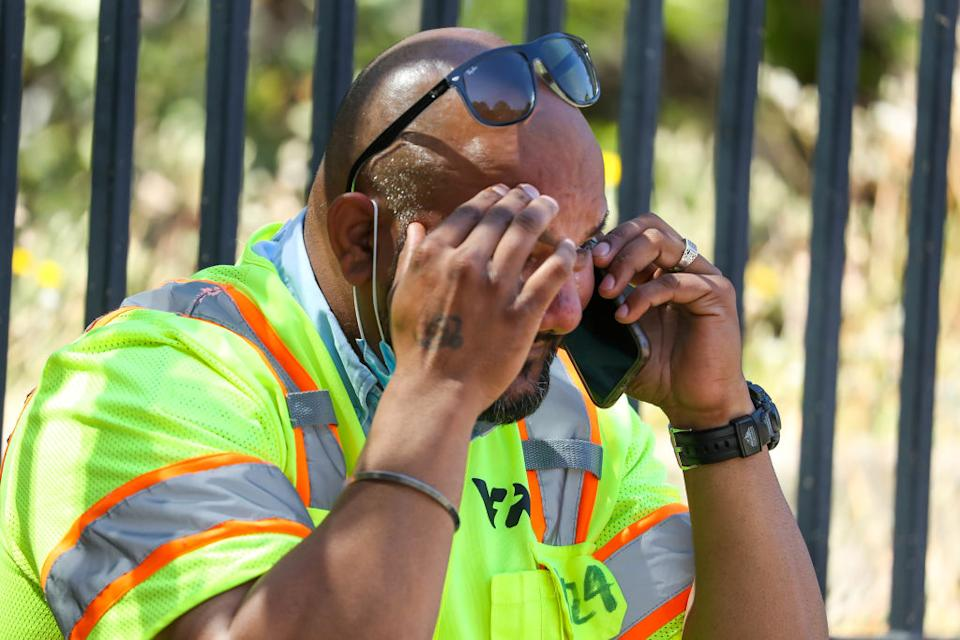 A man cries while sitting on the sidewalk on North First Street near the scene of a shooting at the Valley Transportation Authority's (VTA) light-rail facility in San Jose, California.