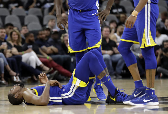 Golden State Warriors' Kevin Durant (35) lies on the court as teammates wait to help him up late in the second half of Game 3 of a first-round NBA basketball playoff series against the San Antonio Spurs in San Antonio, Thursday, April 19, 2018. Golden State won 110-97. (AP Photo/Eric Gay)