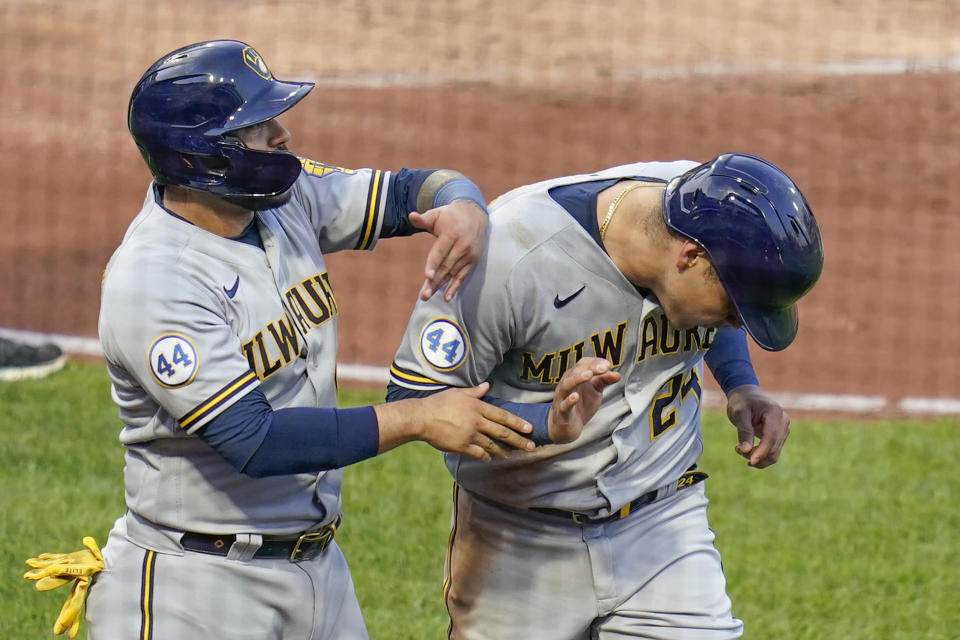 Milwaukee Brewers' Omar Narvaez, left, playfully greets Avisail Garcia, who scored in the Brewers' five-run second inning of a baseball game against the Pittsburgh Pirates, Tuesday, July 27, 2021, in Pittsburgh. (AP Photo/Keith Srakocic)