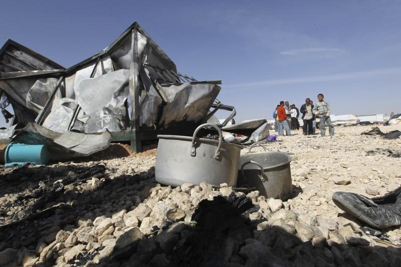 Syrian refugees stand near their damaged belongings at the Al-Zaatri refugee camp