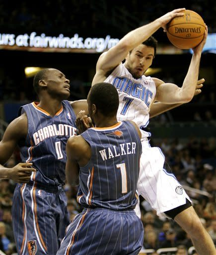 Orlando Magic's J.J. Redick (7) grabs a rebound away from Charlotte Bobcats' Bismack Biyombo (0), of the Republic of Congo, and Kemba Walker (1) during the first half of an NBA basketball game, Tuesday, Jan. 17, 2012, in Orlando, Fla. (AP Photo/John Raoux)