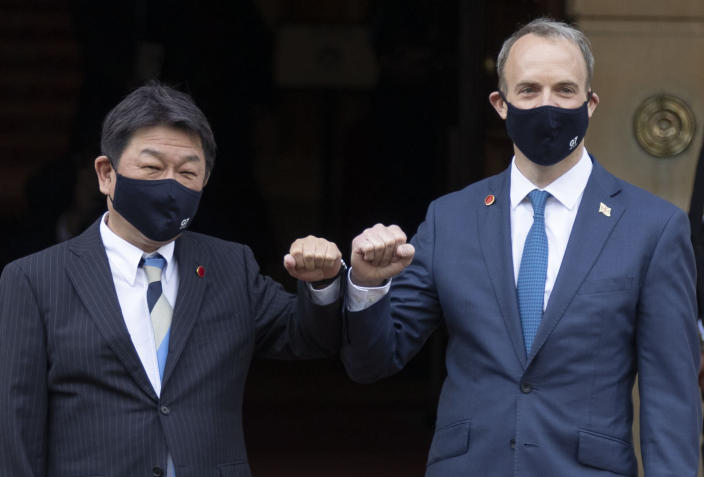 Japan's Foreign Minister Toshimitsu Motegi, left, poses with Britain's Foreign Secretary Dominic Raab at the start of the G7 foreign ministers meeting in London Tuesday May 4, 2021. G7 foreign ministers meet in London Tuesday for their first face-to-face talks in more than two years. (Steve Reigate / Pool via AP)