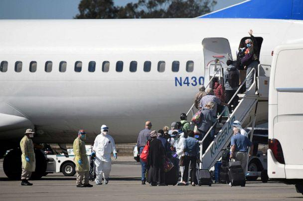 PHOTO: Passengers from the cruise ship Grand Princess board a chartered flight at Oakland International Airport in Oakland, Calif. March 11, 2020. (Kate Munsch/Reuters)