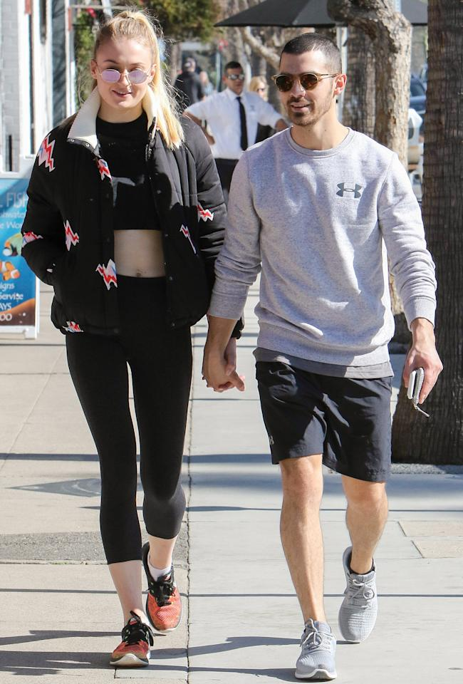 """<p>The couple that works out together, stays together, right? On Valentine's Day, Turner and Jonas both rocked athleisure looks as they ventured out for a hand-in-hand walk in L.A. Turner wore a black bomber (get a similar style from <a rel=""""nofollow"""" href=""""http://click.linksynergy.com/fs-bin/click?id=93xLBvPhAeE&subid=0&offerid=460292.1&type=10&tmpid=20904&RD_PARM1=http%3A%2F%2Fwww.asos.com%2Flazy-oaf%2Flazy-oaf-padded-jacket-with-hearts%2Fprd%2F7579200%3Fiid%3D7579200%2526clr%3DBlack%2526SearchQuery%3D%2526cid%3D2641%2526pgesize%3D187%2526pge%3D0%2526totalstyles%3D187%2526gridsize%3D3%2526gridrow%3D22%2526gridcolumn%3D2&u1=ISSophieTJoeJCoupleMOments2.15JA"""">ASOS</a>), a black crop top, a pair of black leggings, and red sneakers; Jonas had on a long-sleeve Under Armor tee and black shorts.</p>"""
