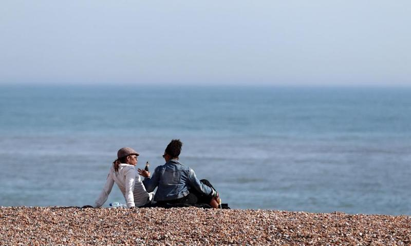 People enjoy the sunshine on the beach in Hastings, East Sussex.