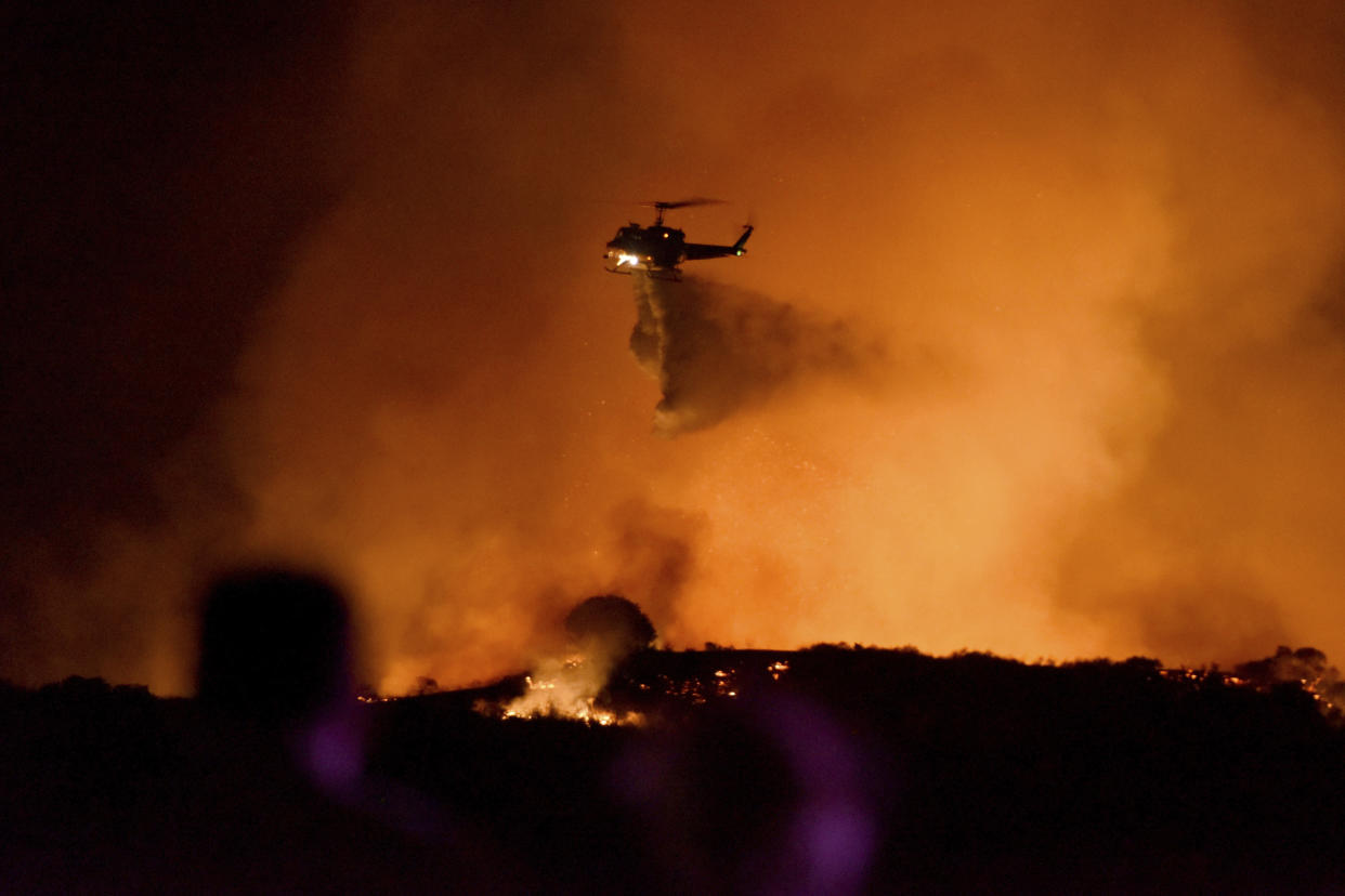 A helicopter drops water on a brushfire in the Santa Monica Mountains in Newbury Park, Calif., Oct. 10, 2019. (Photo: Michael Owen Baker/AP)