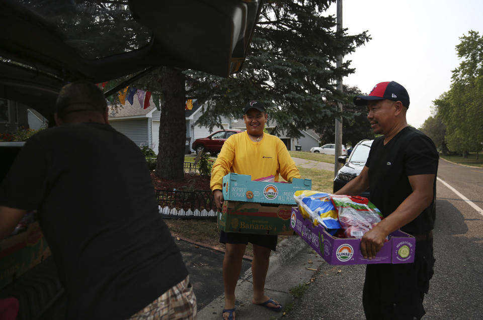 Jalue Dorje, center, helps load a car with food that was blessed during a ceremony honoring Guru Rinpoche, the Indian Buddhist master who brought Tantric Buddhism to Tibet, on Tuesday, July 20, 2021, in Columbia Heights, Minn. The food was donated to families across the Minneapolis suburbs. (AP Photo/Jessie Wardarski)