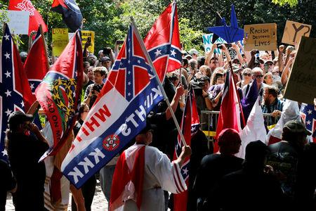 FILE PHOTO: Members of the Ku Klux Klan face counter-protesters as they rally in support of Confederate monuments in Charlottesville Virginia