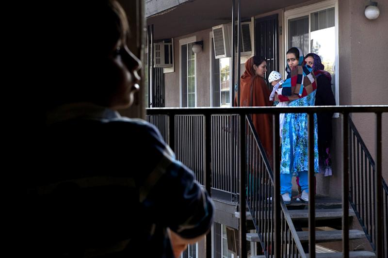 Malalai Rafi, far right, joins other Afghan women to bid good-bye to Mohammad Eltaf Stana, 5 ½, left, and his family as they move from Skyview Villa Apartments on Mon. Nov. 23, 2015. Mohammad's mother had been hit by a car while walking his sister home from school along Edison Avenue, the same street Malalai's husband was killed and son severely injured when a motorist hit them. Mohammad's family did not feel safe living in the complex. Many of the Afghan women who fled the Taliban with their SIV husbands rely heavily on one another. They feel isolated, most are unable to speak English, cannot drive and have small children they can't afford daycare for. (Photograph by Renée C. Byer/The Sacramento Bee)