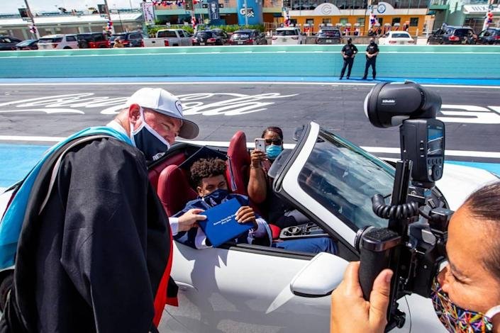 Principal David Pugh poses for a photo with a senior after handing him his diploma on the race track during the Christopher Columbus High School senior graduation ceremony at Homestead-Miami Speedway, in Homestead, Florida on Saturday, June 20, 2020.