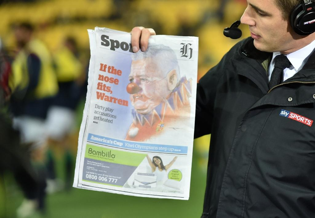 A television host holds up a newspaper with an image of British and Irish Lions coach Warren Gatland depicted as a clown before their rugby union match against the Wellington Hurricanes at Westpac Stadium in Wellington on June 27, 2017. (AFP Photo/PETER PARKS)