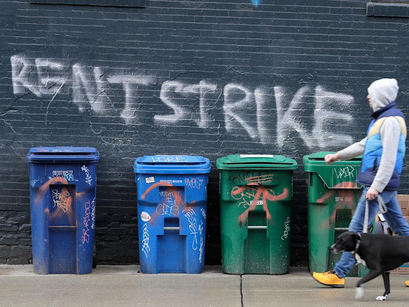 "A pedestrian walks past graffiti that reads ""Rent Strike"" Wednesday, April 1, 2020, in Seattle, Washington.(AP Photo:Ted S. Warren)"