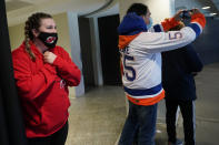 A new Jersey Devils fan reacts as she sees the ice for the first time as New. York Islanders fan snaps a cell phone photo before an NHL hockey game between the New Jersey Devils and the New York Islanders, Tuesday, March 2, 2021, in Newark, N.J. It was the first time fans were allowed in the Prudential Center under New Jersey's more relaxed COVID-19 rules. (AP Photo/Kathy Willens)