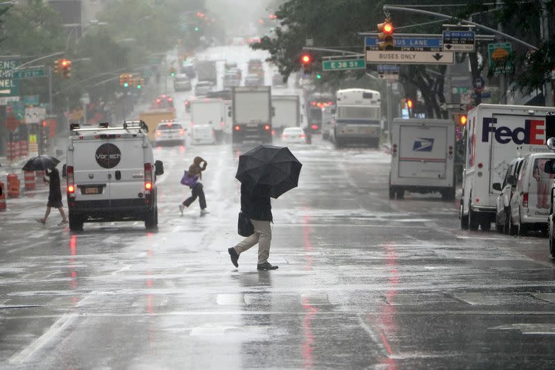 People with umbrellas cross a street as the city starts to feel the effects of Tropical Storm Isaias