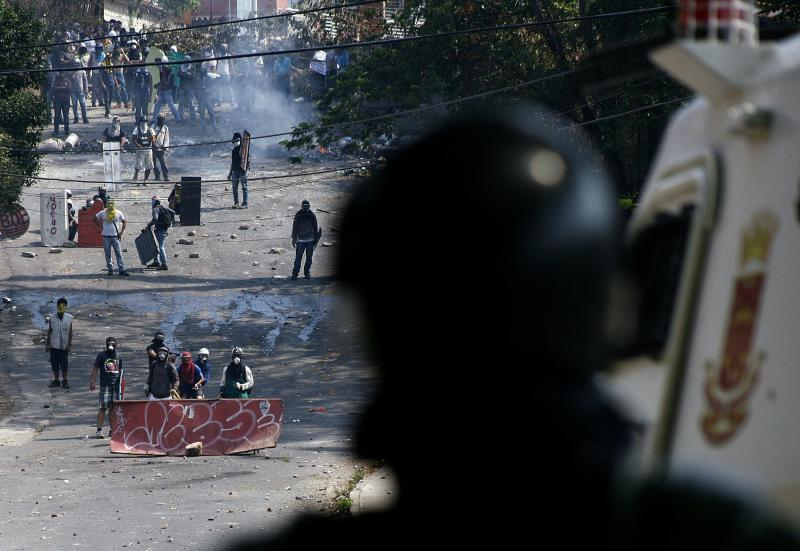 Anti-government protesters clash with a member of the National Guard during a protest in San Cristobal