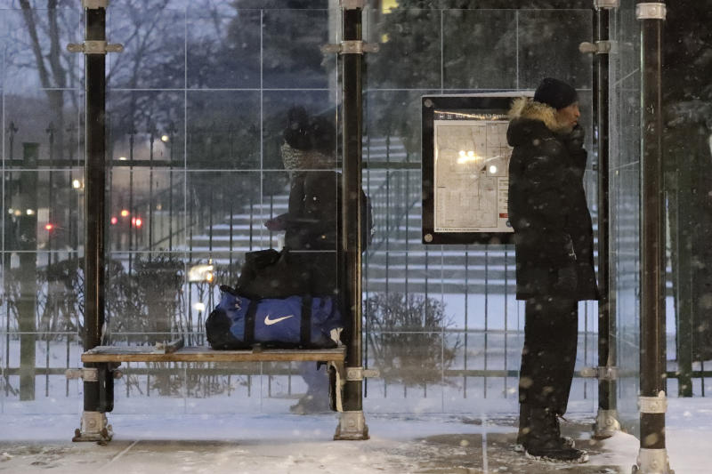 A pedestrian waits for a bus at a bus stop during a snow day in Chicago, Friday, Jan. 17, 2020. Hundreds of flights were canceled as a winter storm hits the city during evening commute Friday, creating a sloppy rush hour. (AP Photo/Nam Y. Huh)