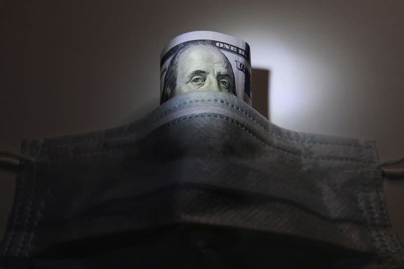 FILE PHOTO: A U.S. dollar banknote is pictured behind a protective mask in this illustration
