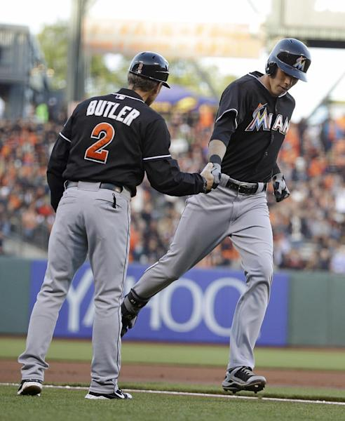 Miami Marlins' Christian Yelich, right, is greeted by third base coach Brett Butler after hitting a home run off San Francisco Giants pitcher Yusmeiro Petit in the first inning of a baseball game Friday, May 16, 2014, in San Francisco. (AP Photo/Eric Risberg)