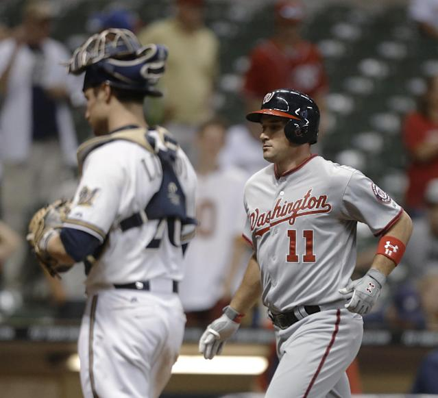 Washington Nationals' Ryan Zimmermann (11) crosses home after he hit a two-run home run against the Milwaukee Brewers during the 16th inning of a baseball game Wednesday, June 25, 2014, in Milwaukee. The Brewers' Jonathan Lucroy is at left. (AP Photo/Jeffrey Phelps)