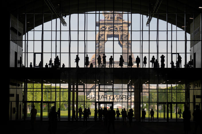 """FILE - In htis Wednesday, June 9, 2021 file photo, visitors gather during a presentation visit of the """"Grand Palais Ephemere"""", with the Eiffel Tower in the background, in Paris. Europe is opening up to Americans and other visitors after more than a year of COVID-induced restrictions. European governments hope to lure back tourists - and their dollars - back to the continent's trattorias, vistas and cultural treasures. (AP Photo/Francois Mori, File)"""