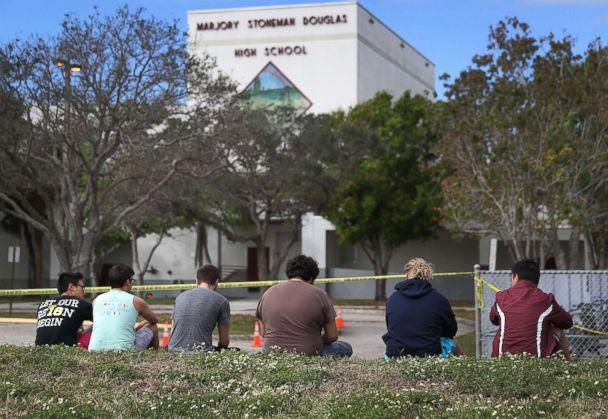 PHOTO: People look on at the Marjory Stoneman Douglas High School, Feb. 18, 2018 in Parkland, Fla. (Joe Raedle/Getty Images)